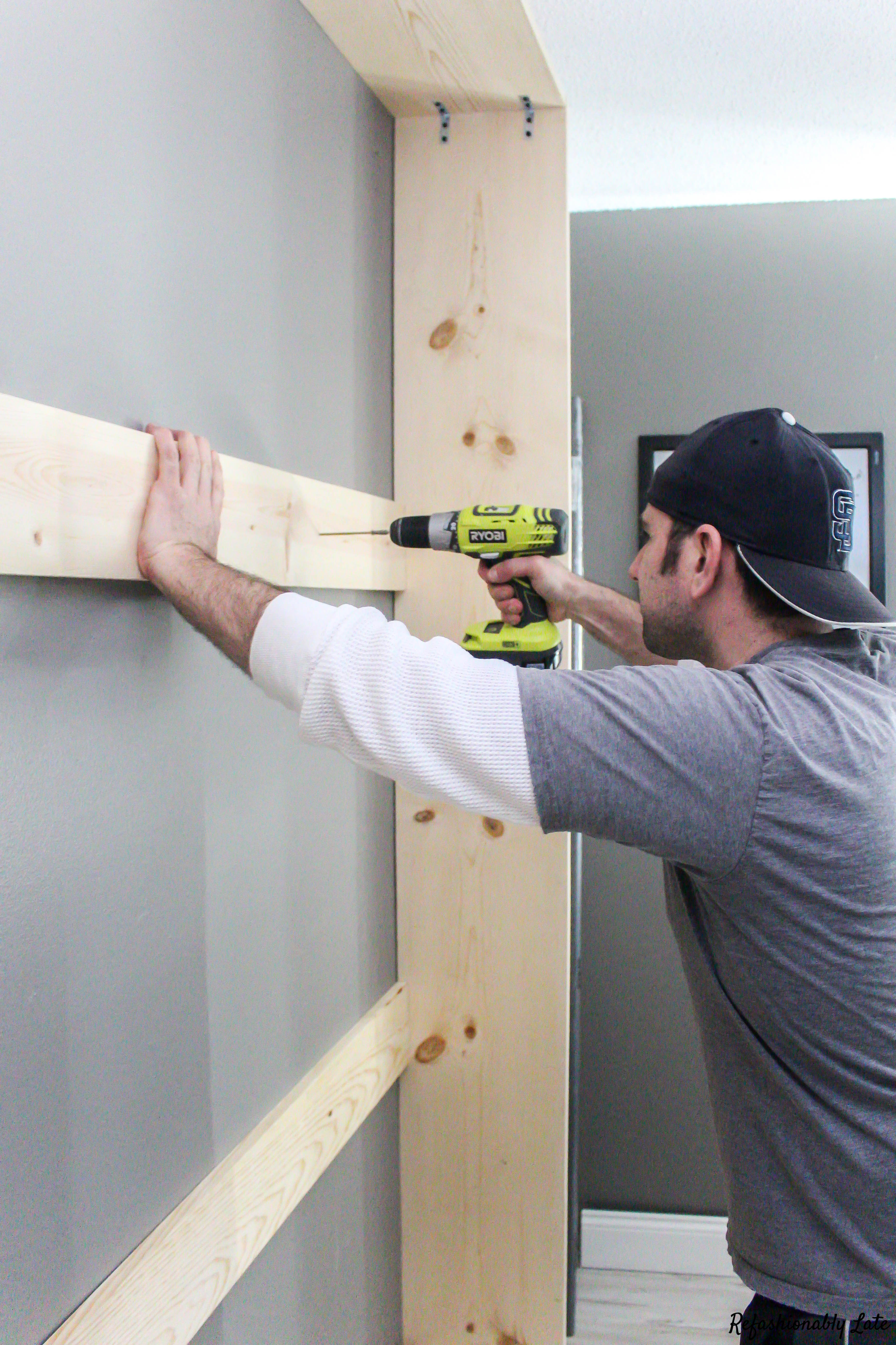 man drilling screws into frame of murphy bed against dark grey wall