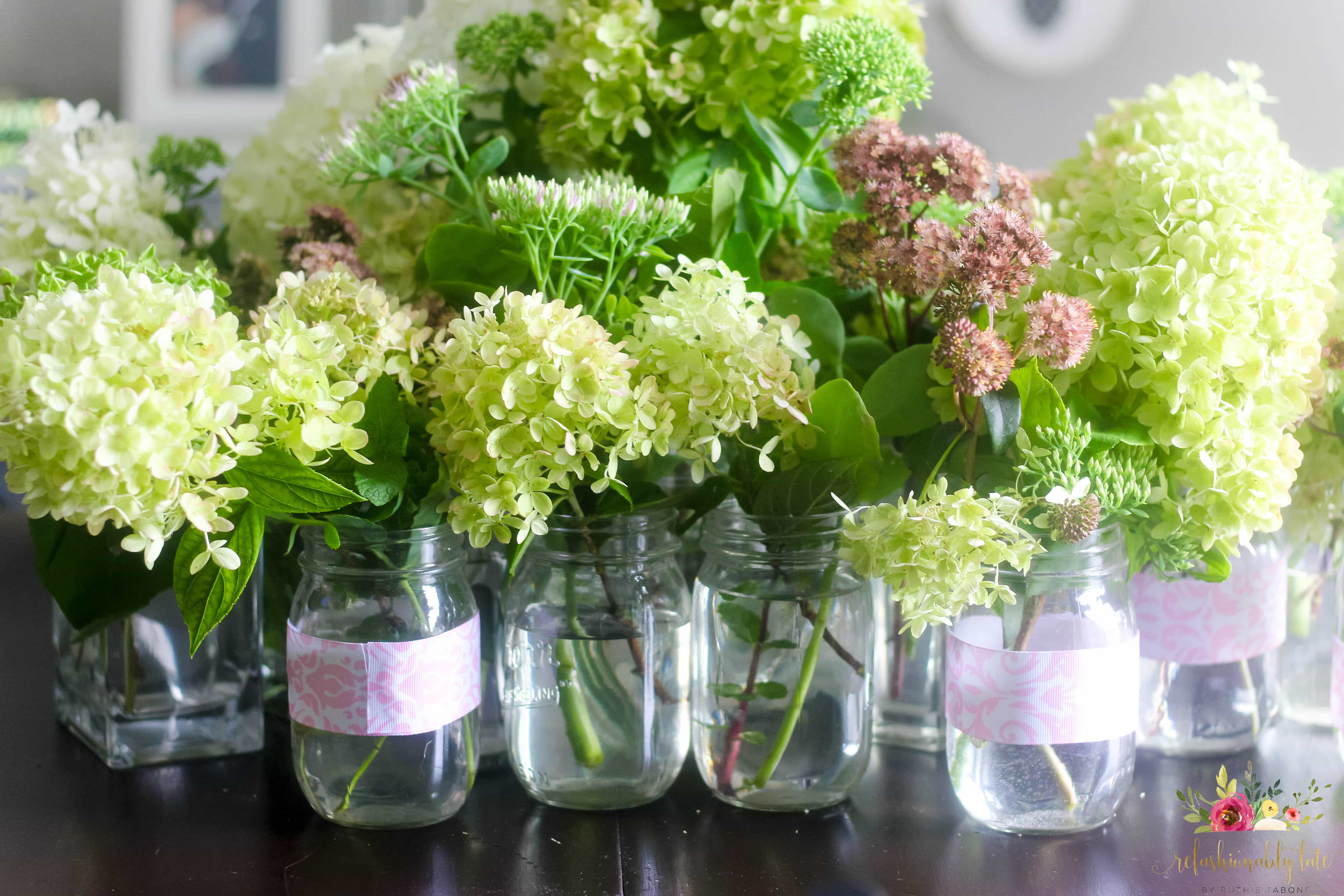 multiple vases with hydrangeas sitting on a table