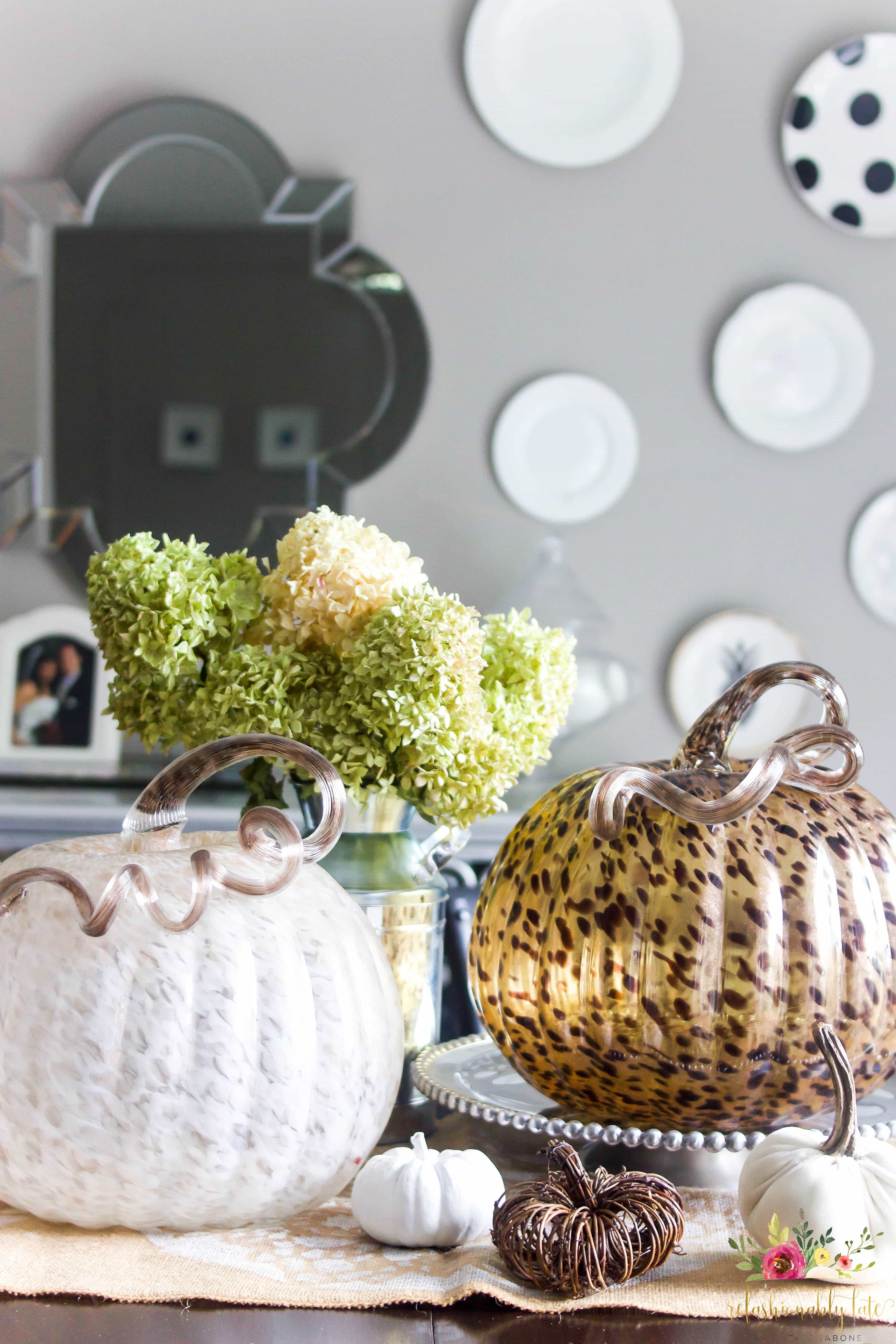 Two glass pumpkins surrounded by various small pumpkins sitting on top of a burlap table runner