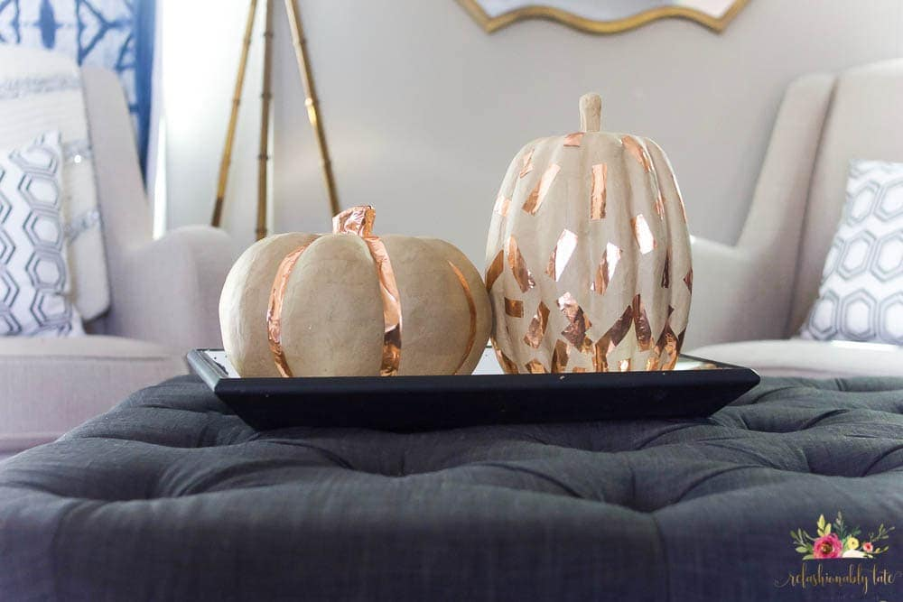 two paper mache pumpkins with copper washi tape decorations on an ottoman