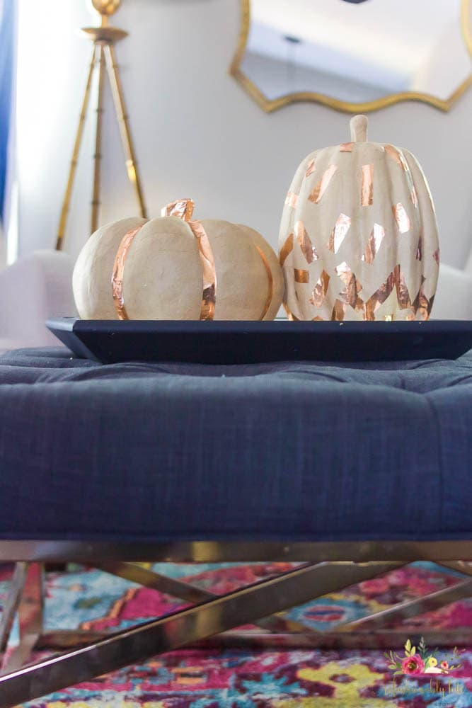 two paper mache pumpkins with copper washi tape designs sitting on top of an ottoman