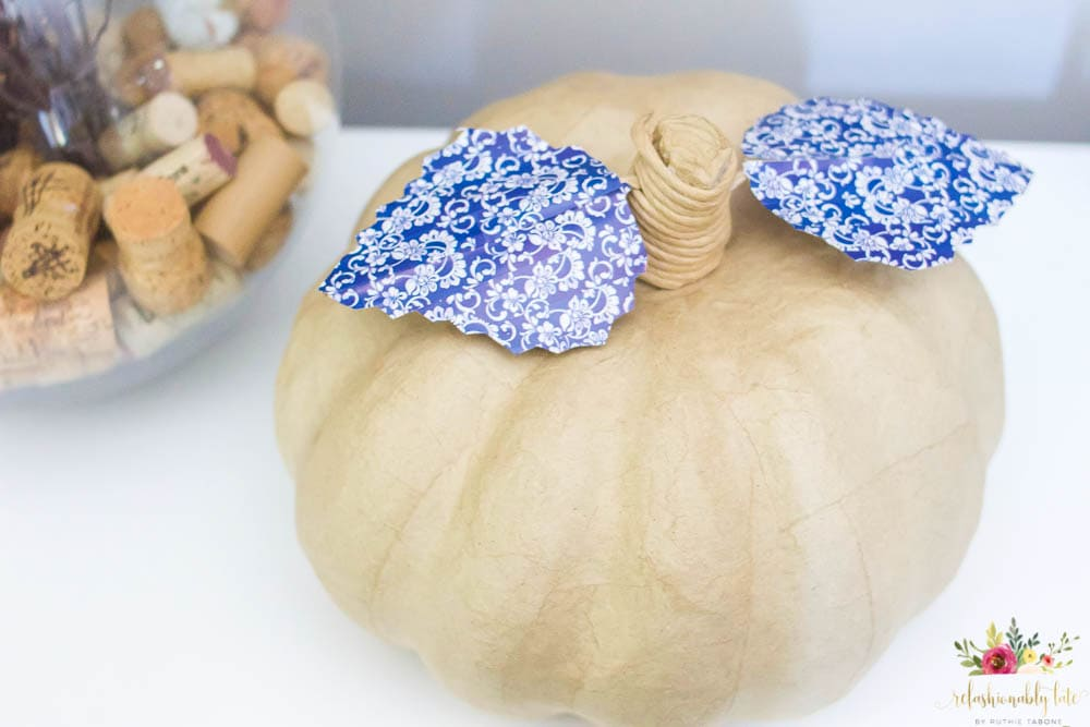 paper mache pumpkin with blue and white leaves on top of a table