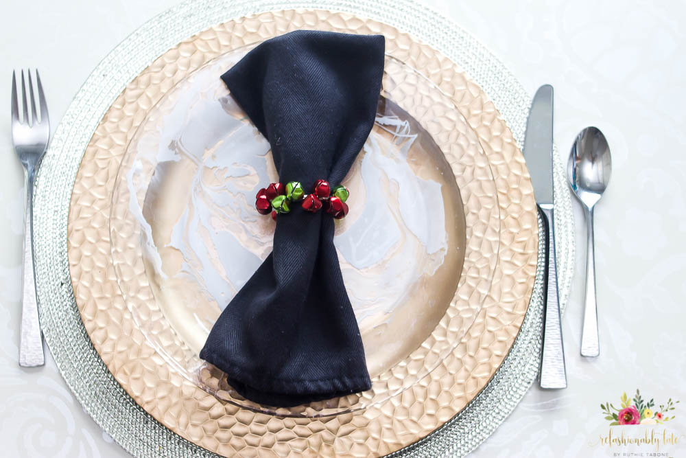 gold charger with marbled plate on top with a black napkin and holiday bells napkin ring