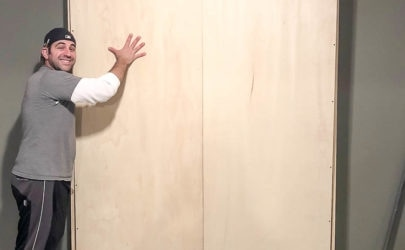 murphy bed being held up to the wall by a handsome man