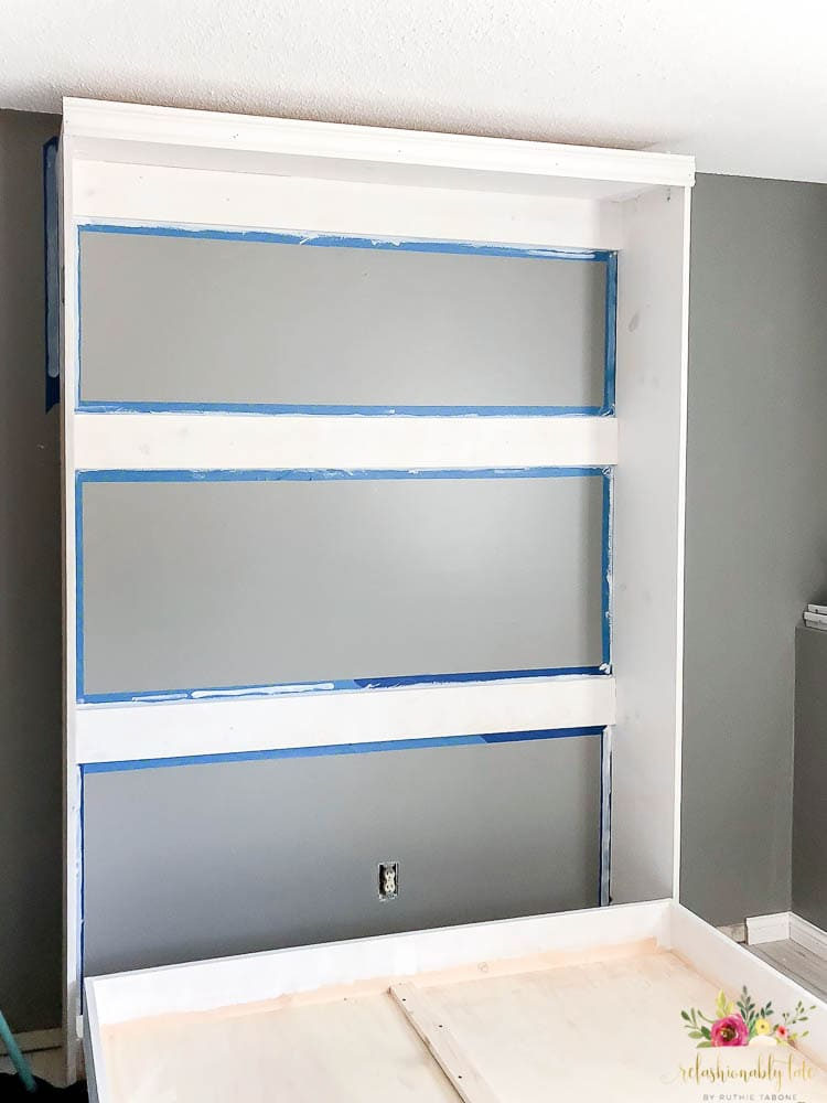murphy bed frame against dark gray wall with painters tape around the edges and primed white