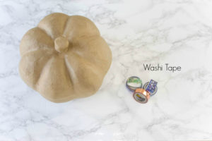 paper mache pumpkin and washi tape sitting on top of marble counter top