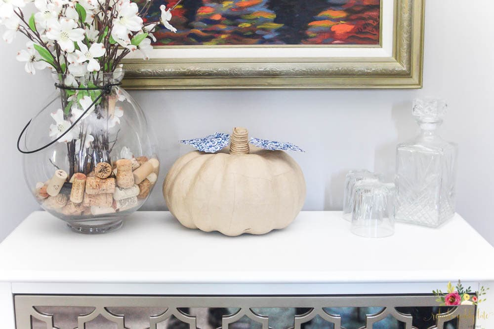 paper mache pumpkin with blue and white patterned leaves on a white dresser