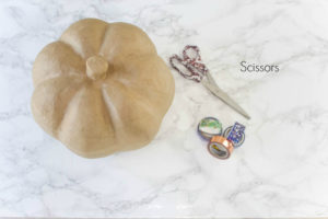 paper mache pumpkin washi tape and damask scissors sitting on top of a marble counter top
