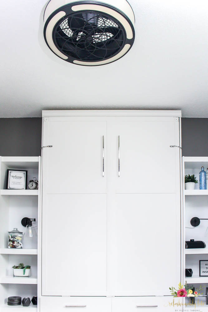 white murphy bed with two shelves on either side and a stile fan and light in one on the ceiling