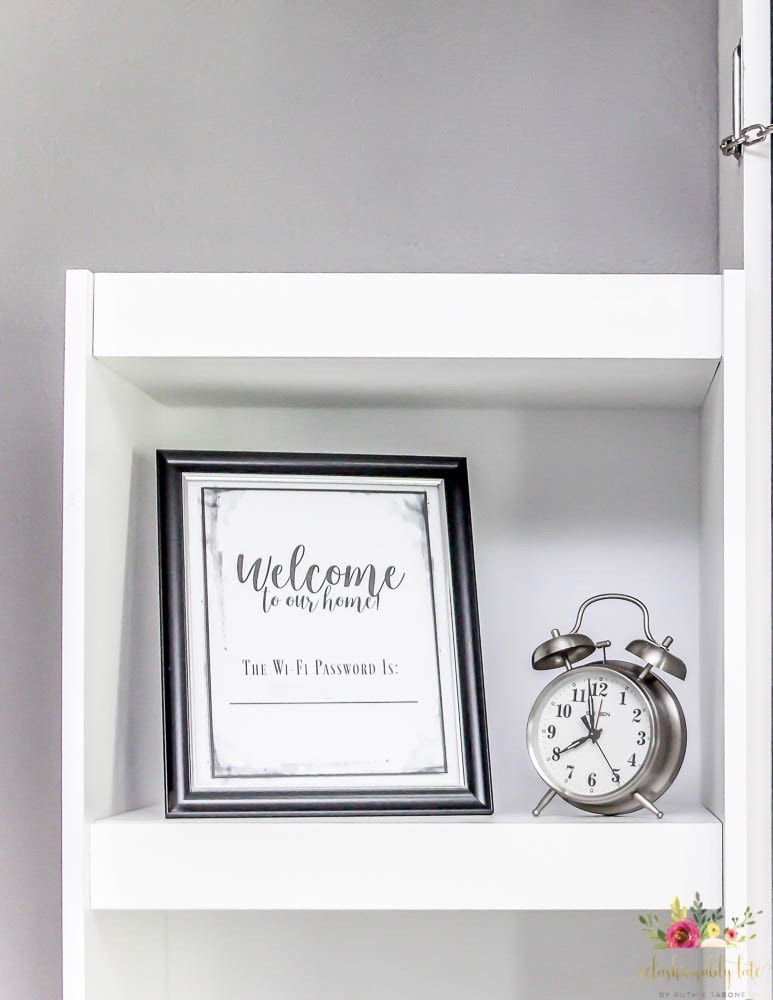 picture frame with text Welcome to our home the wifi password is sitting on white shelf with silver clock next to it