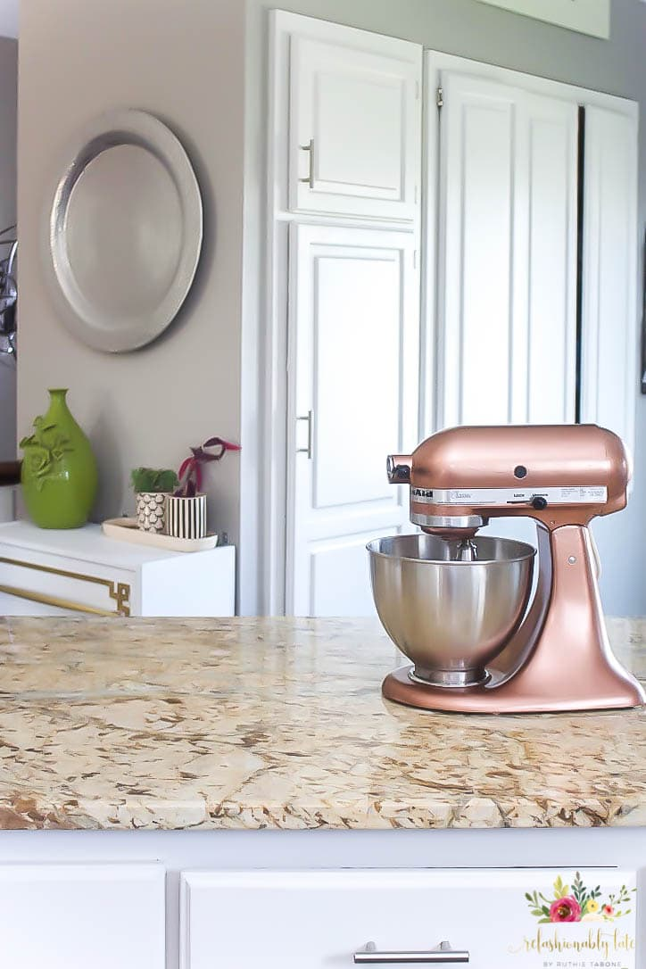 Copper KitchenAid Mixer sitting on top of a tan granite counter top with white cabinets and gray walls and white cabinets in the background