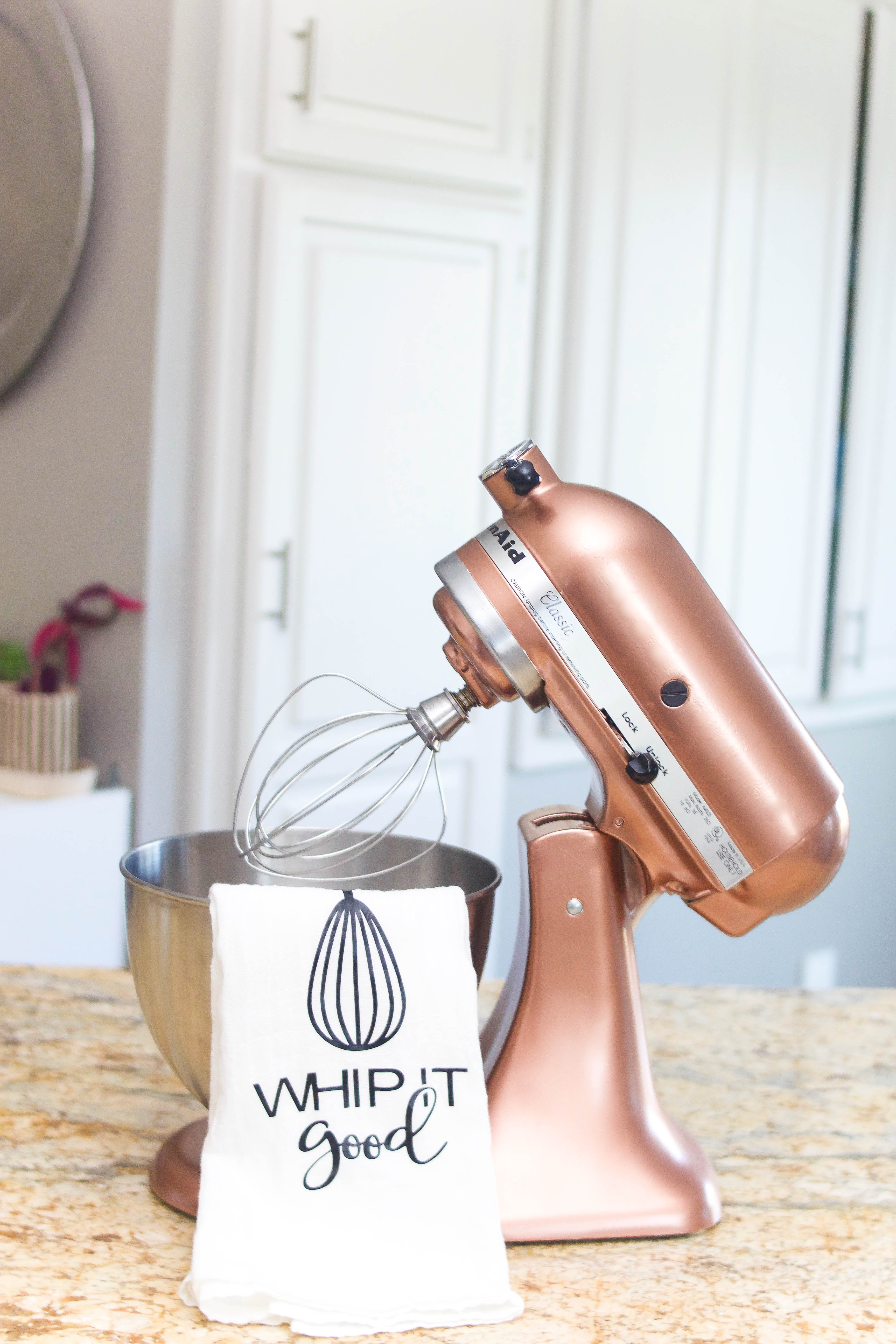 copper KitchenAid sitting on tan granite with white cabinets in the background and a towl hanging from it reading Whip It Good