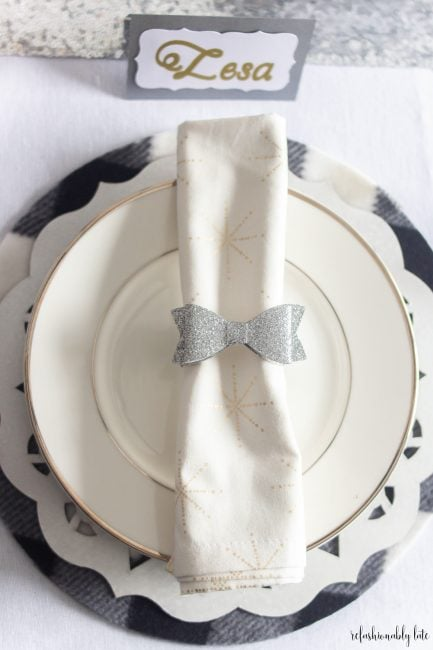 white tablecloth with buffalo plaid place mat and white charger with a plate and napkin folded with a sparkly bow napkin ring
