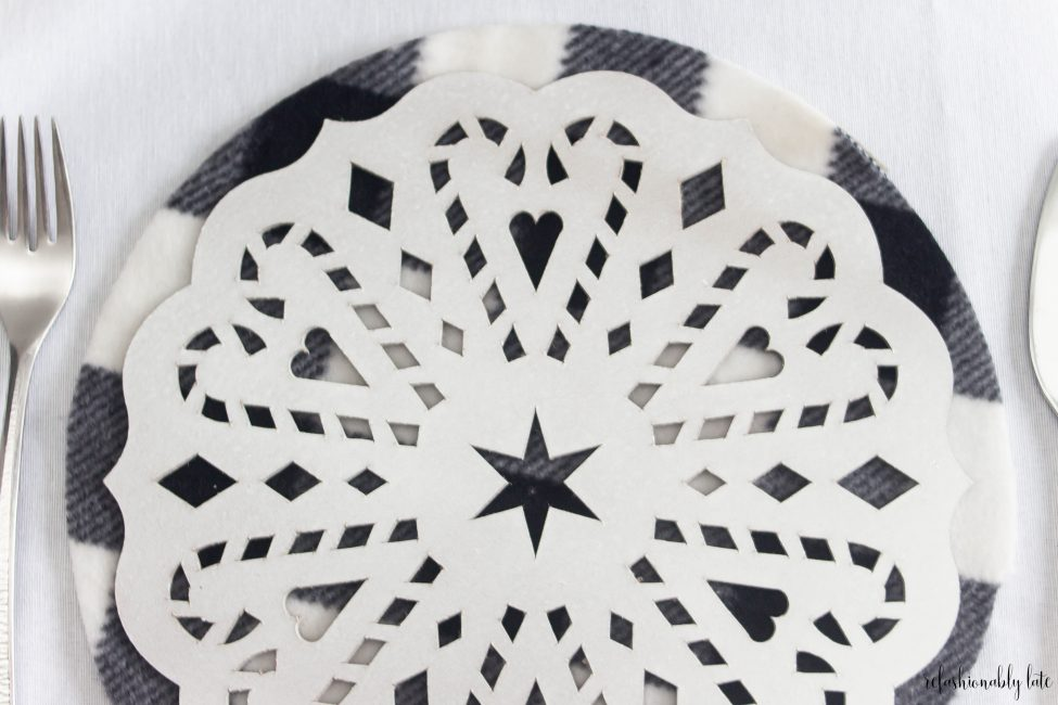 white tablecloth with black and white buffalo plaid place mat and white DIY charger with hearts diamonds starts and candy canes cut out