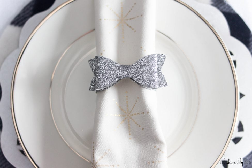 white plate with a white napkin with gold starts and a silver bow napkin ring