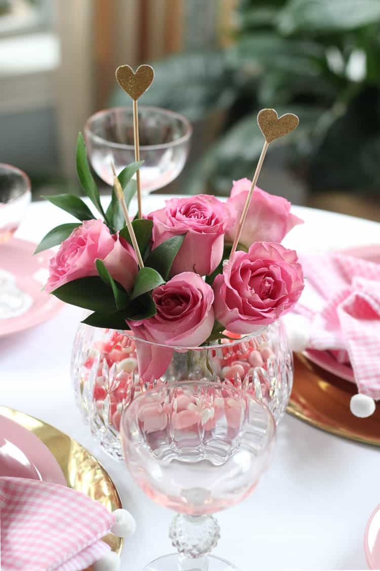 beautiful crystal vase with pink roses inside and gold chargers with pink plates on a white tablecloth