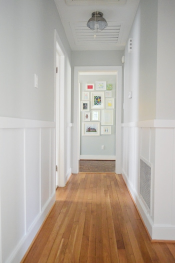 white board and batten in a hallway with wood floors and artwork at the end of the hallway