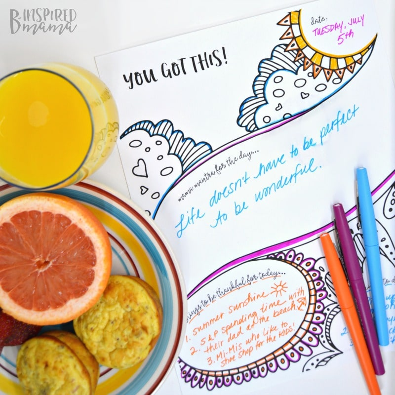 sheet of paper with colorful writing on it and a glass of orange juice and fruit and muffins