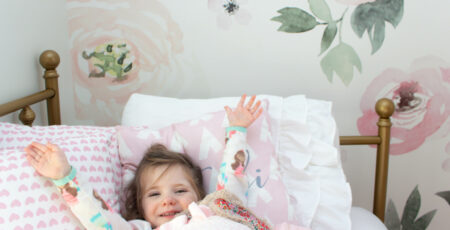 tips on transitioning to big kid bed with little girl in gold bed with floral background