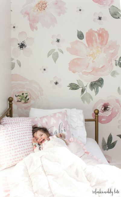 little smiling girl laying in a gold daybed with floral wallpaper in the background