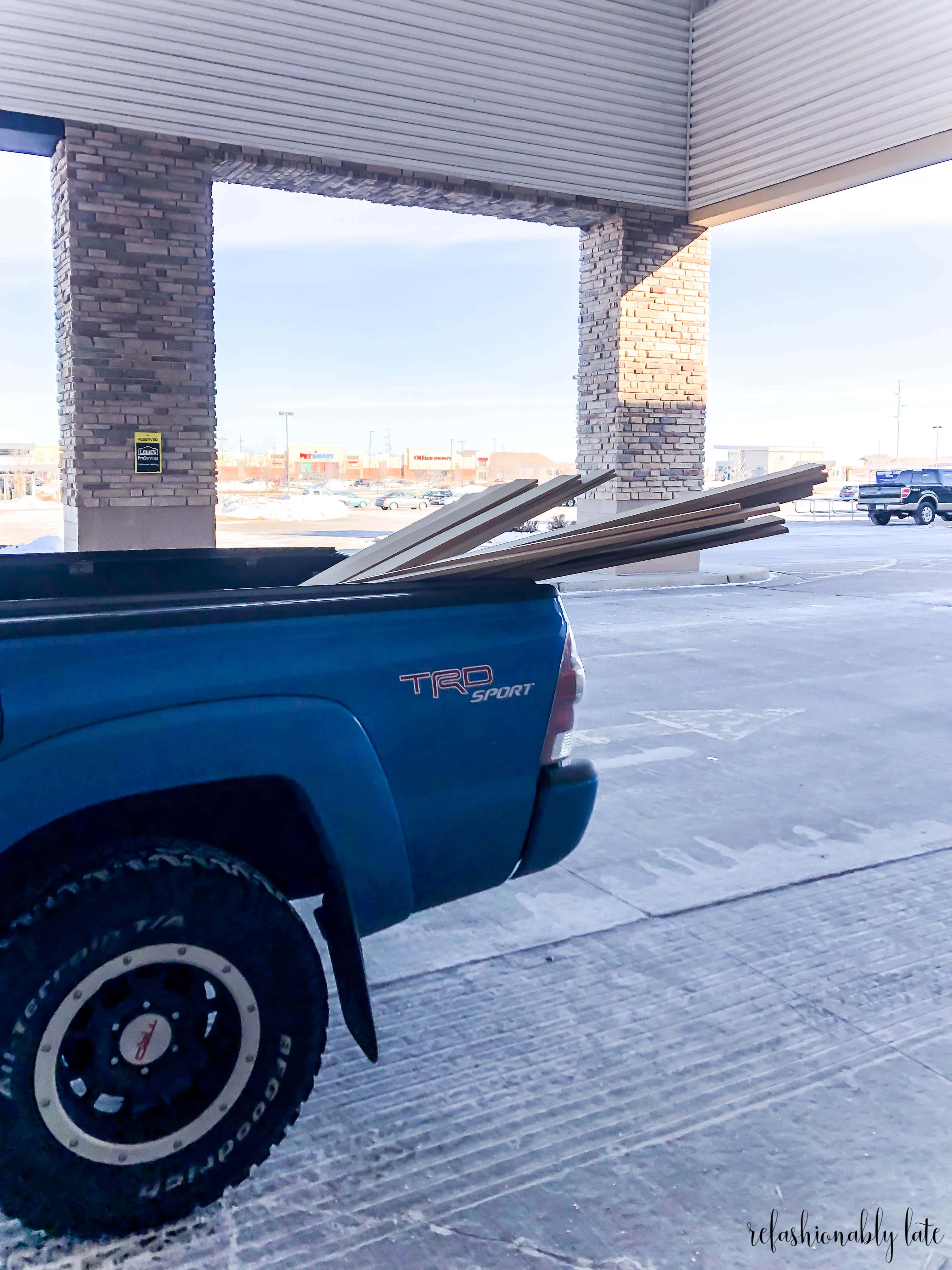 blue truck with MDF boards inside under a Lowes awning