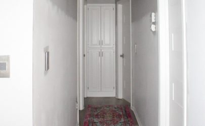 hallway with colorful rug and gray and white walls and white doors and trim
