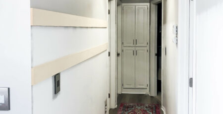 photo of hallway with colorful rugs and white and gray walls and two mdf boards nailed into the wall