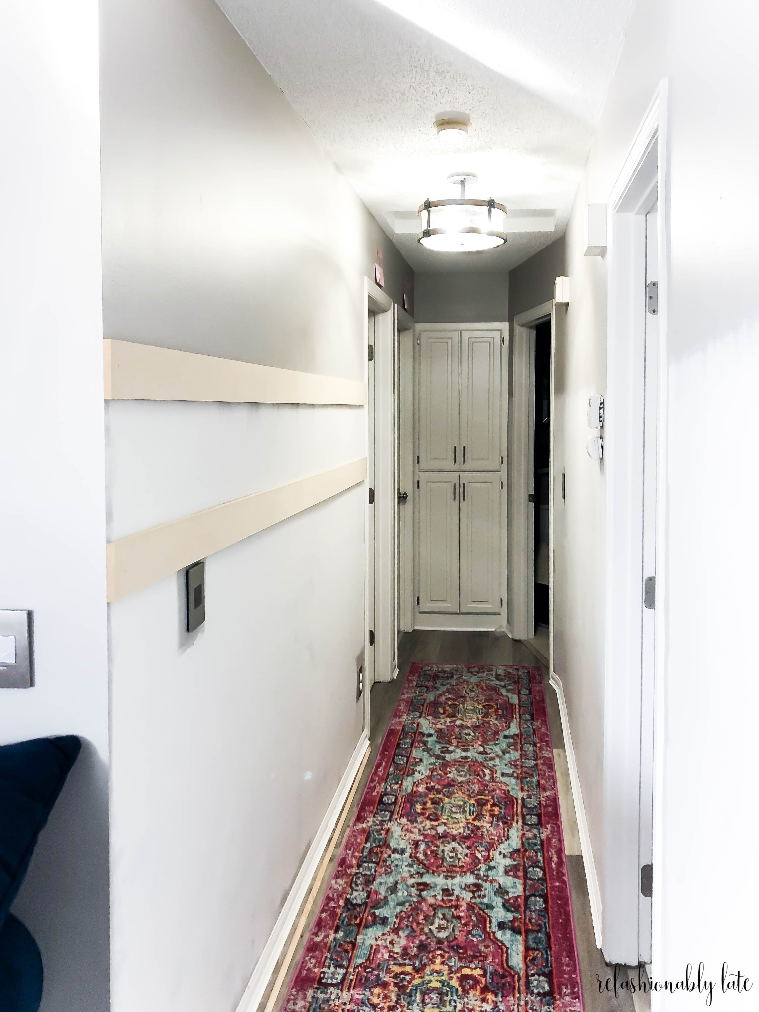 photo of hallway with colorful rugs and white and gray walls and two mdf boards nailed into the wall preparing for board and batten for the $100 Room Challenge