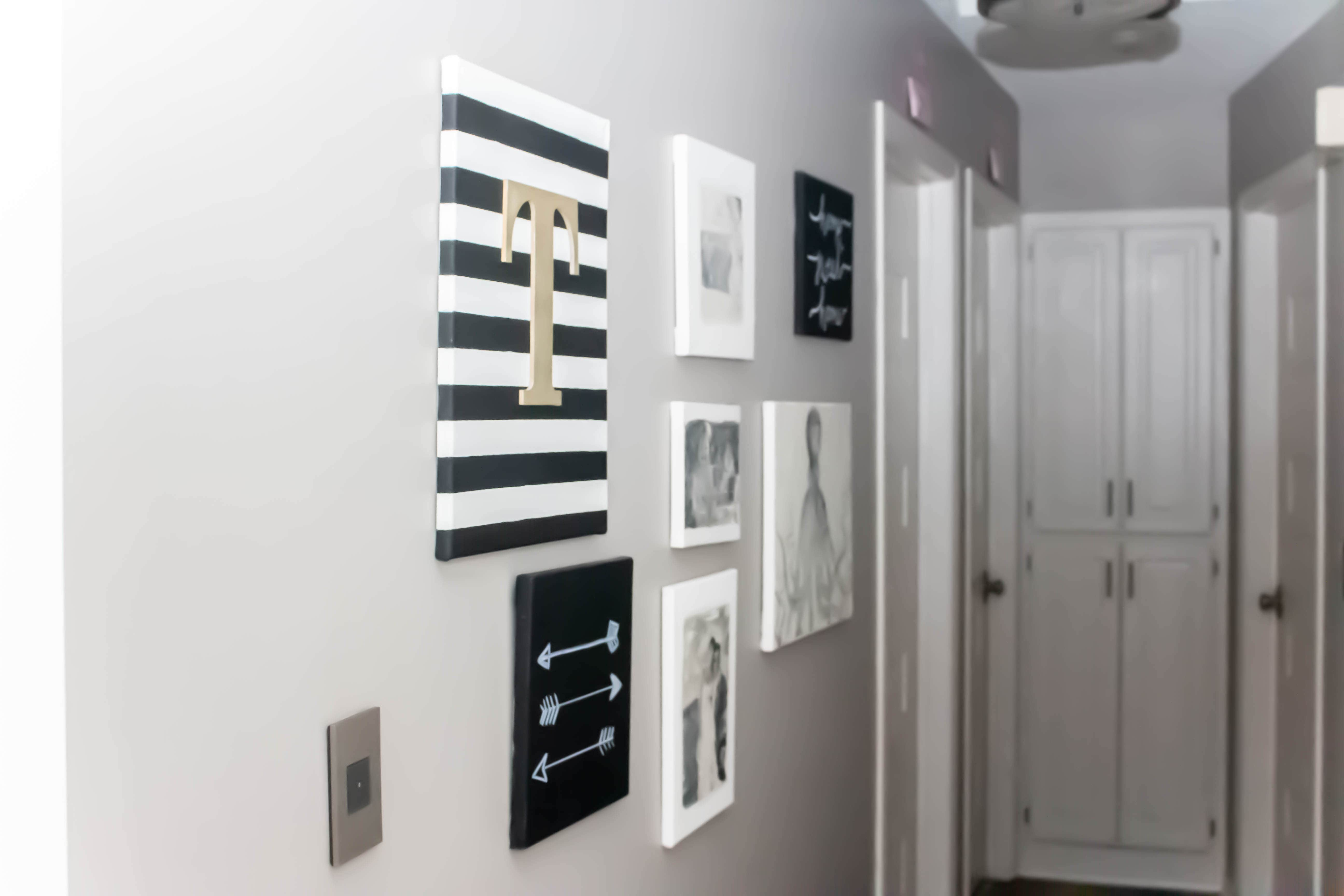 hallway with gray walls and white woodwork with gallery wall of various canvas art