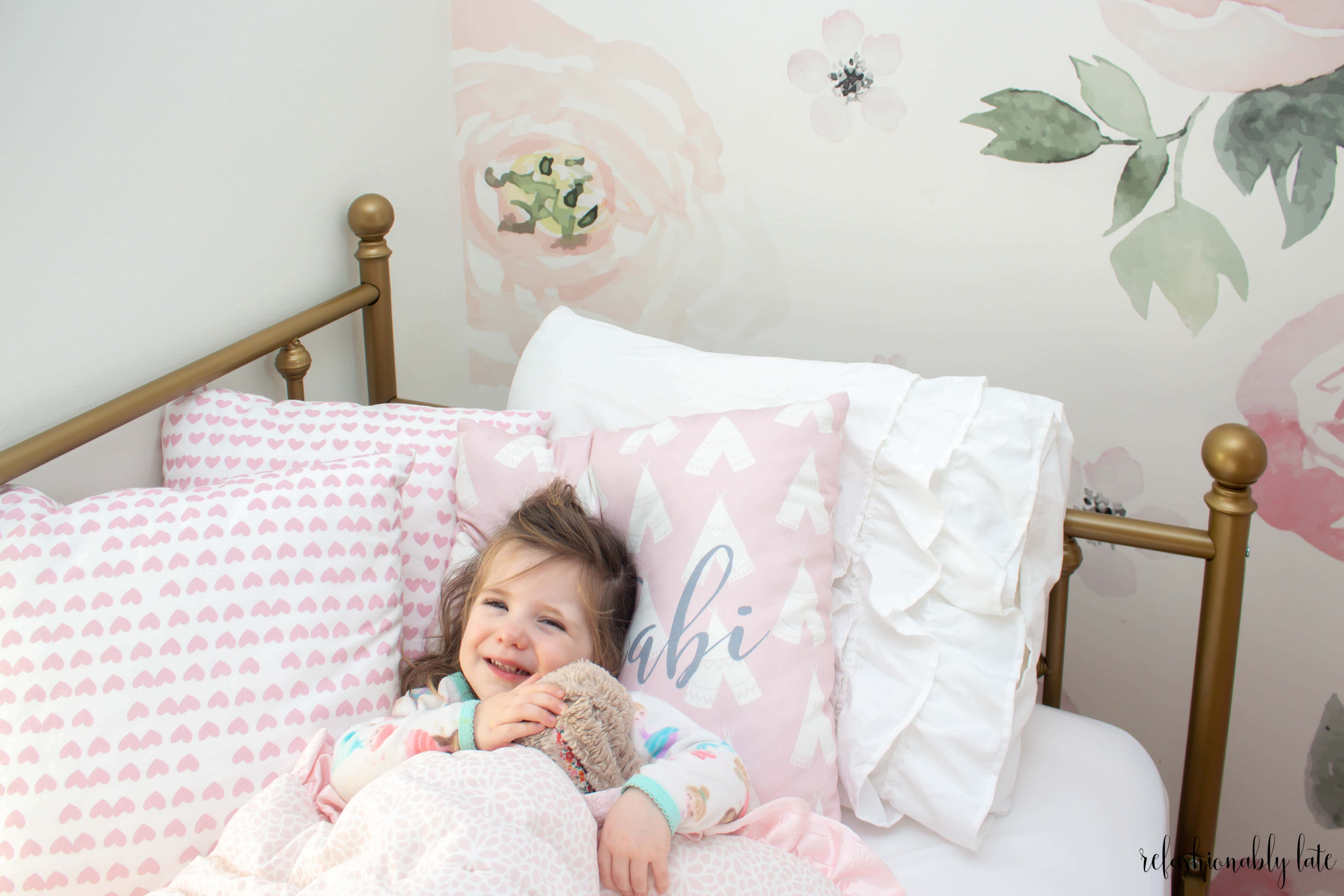 gold daybed with pillows and little girl snuggling a bunny