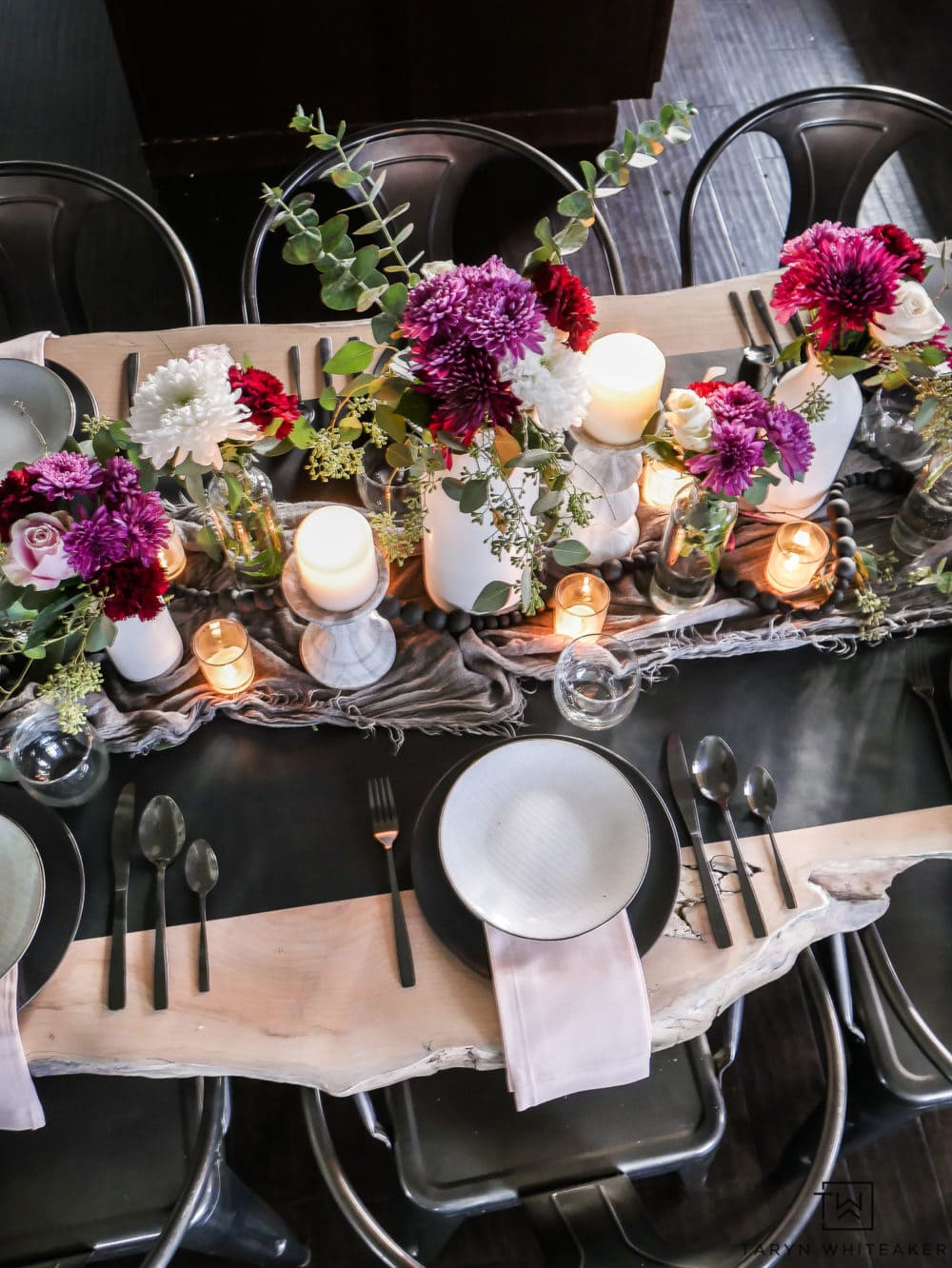 dramatic valentines day tablescape with black table runner and deep red and purple flowers with black chargers and white plates