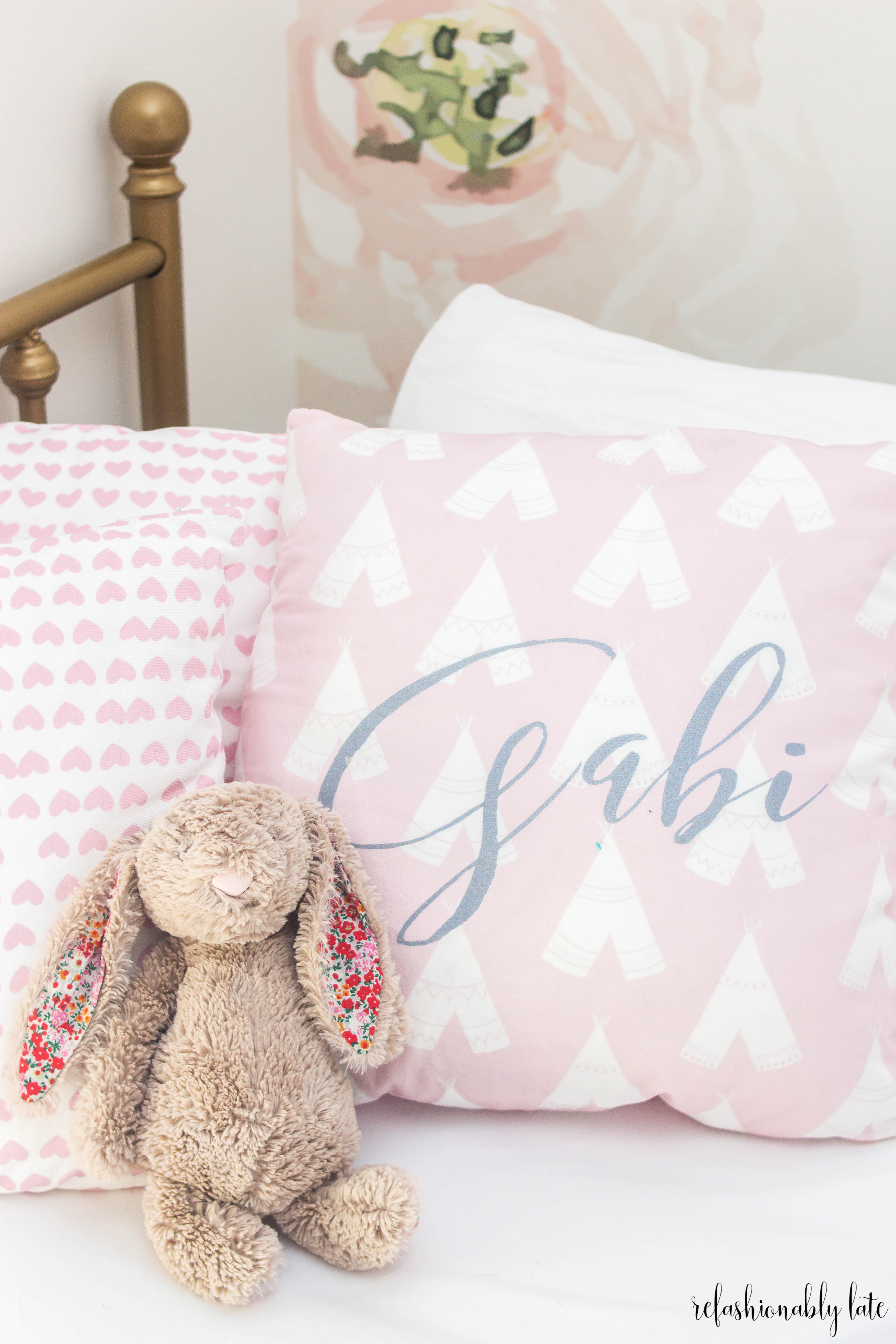 pink pillows with Gabi written on one a stuffed bunny and gold bed