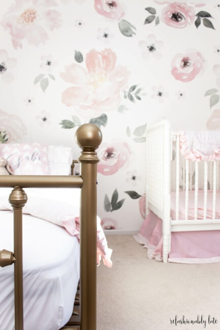 gold bed frame with floral wallpaper background and a white crib