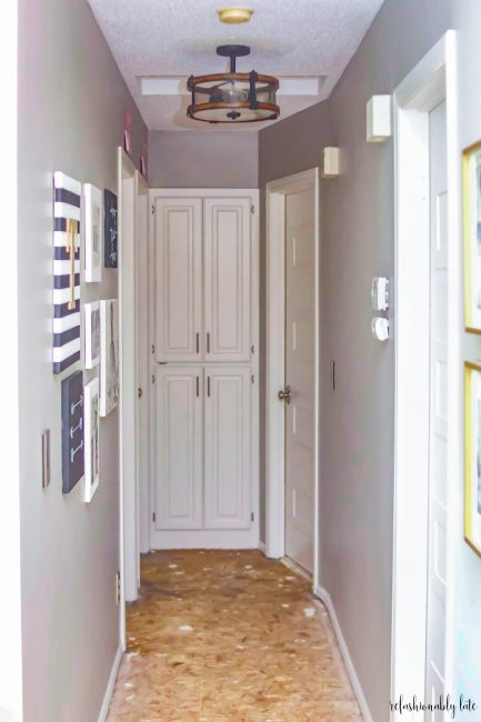 hallway with white doors and cabinets gray walls and gallery wall and luan floors