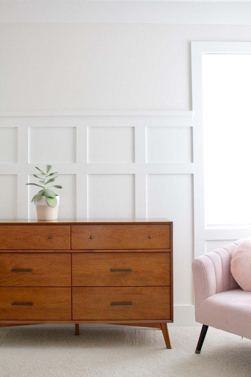 natural wood dresser with white board and batten on a white wall with a pink chair