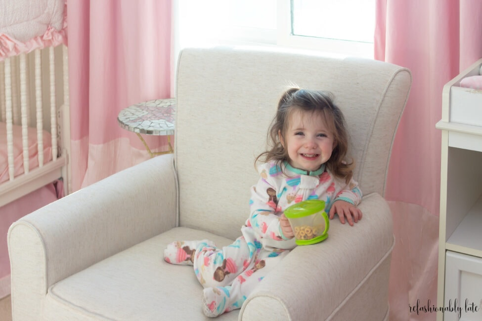 smiling little girl sitting in a tan rocker with pink drapes behind her