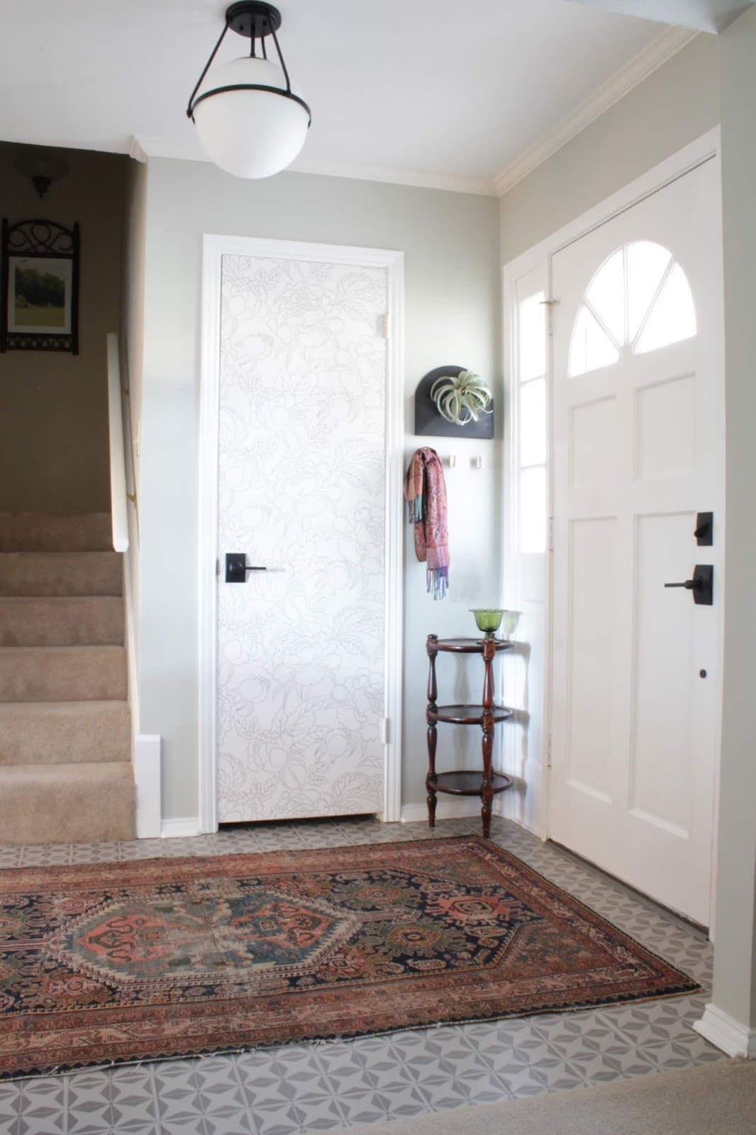White front door and floral white closet door with a rug on the floor and tile floor