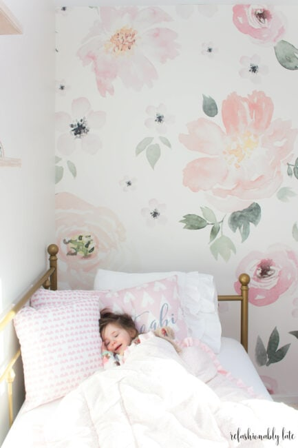 tips on transitioning to big kid bed and a little girl laying in gold daybed with floral wallpaper background
