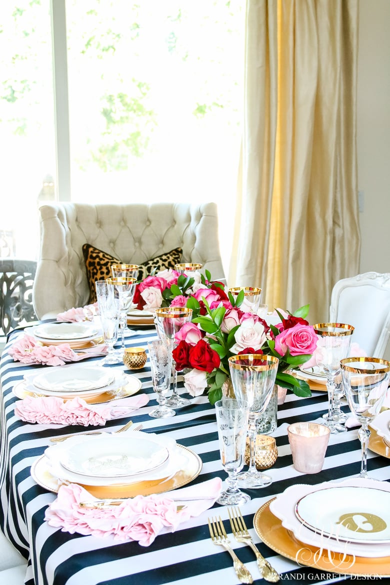 black and white striped tablecloth with white plates and gold chargers and red pink and white floral centerpiece