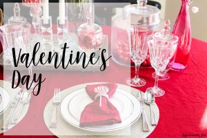 Valentines day table with silver and white place settings red table cloth and red napkins and crystal decor with red candy