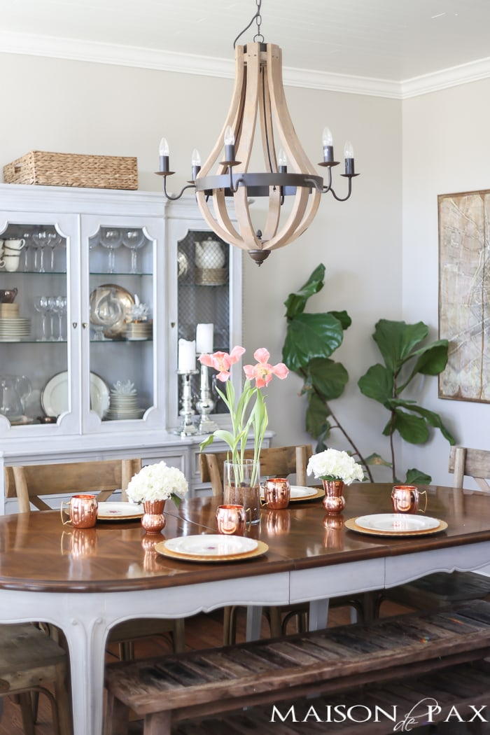 dining room with wooden chandelier and copper elements added to a tablescape