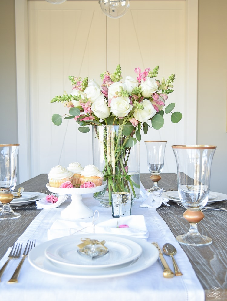 grey table with cream and light pink flowers and gold rimmed glasses with white table settings