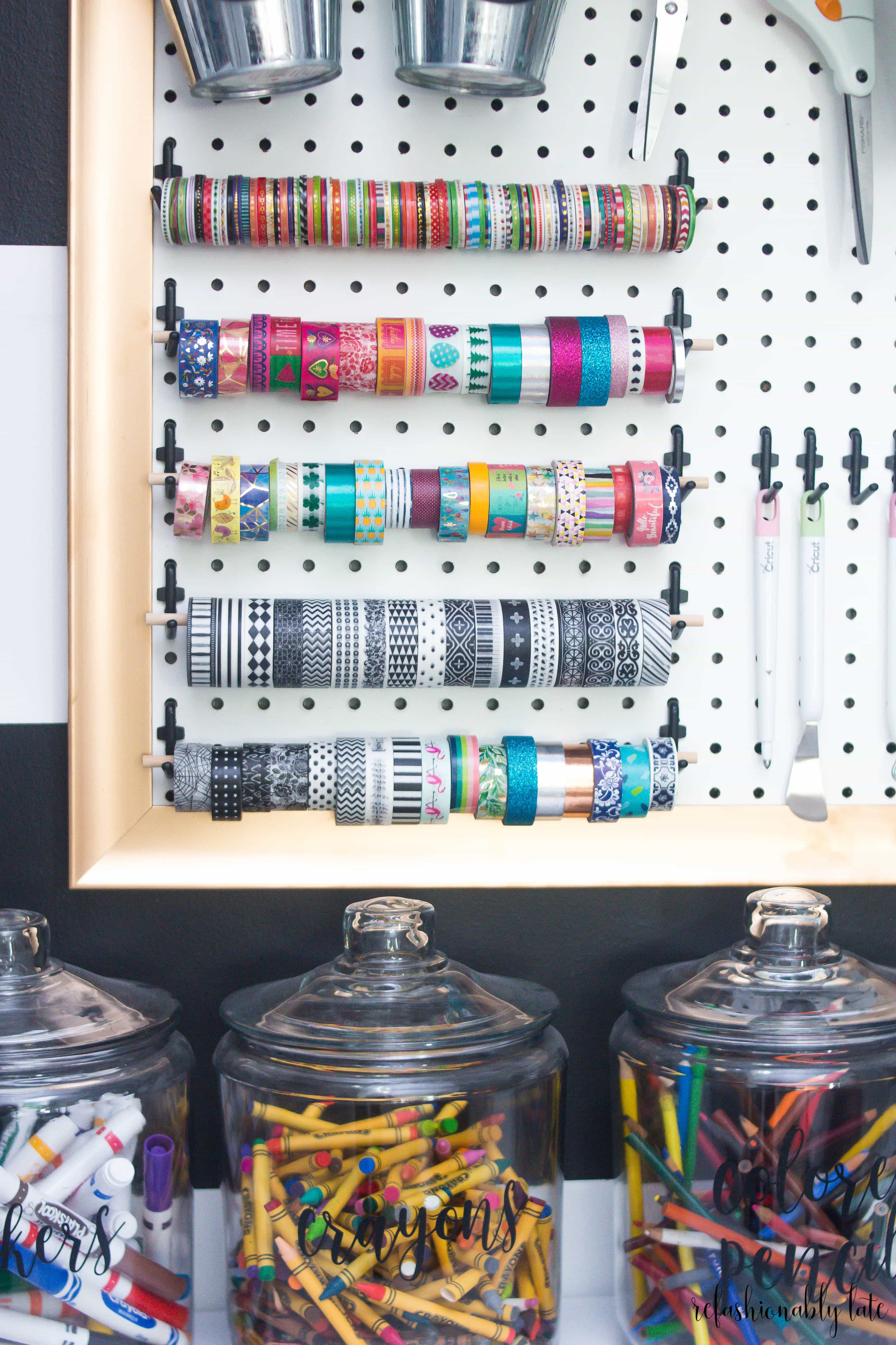 white pegboard with a gold frame and multiple washi tape hanging from it along with cricut tools and three jars below