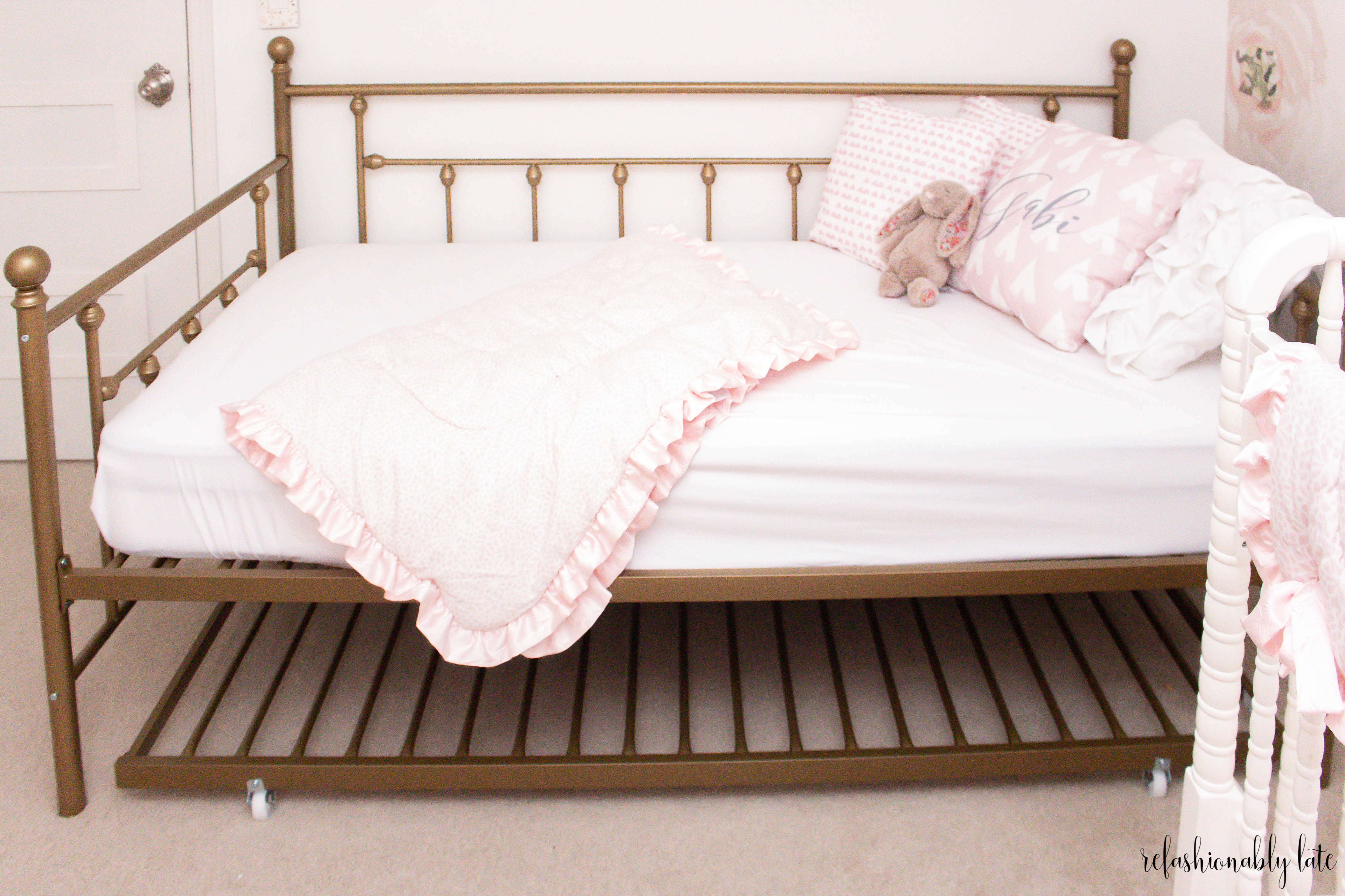 gold daybed with trundle underneath and white and pink sheets blankets and pillows