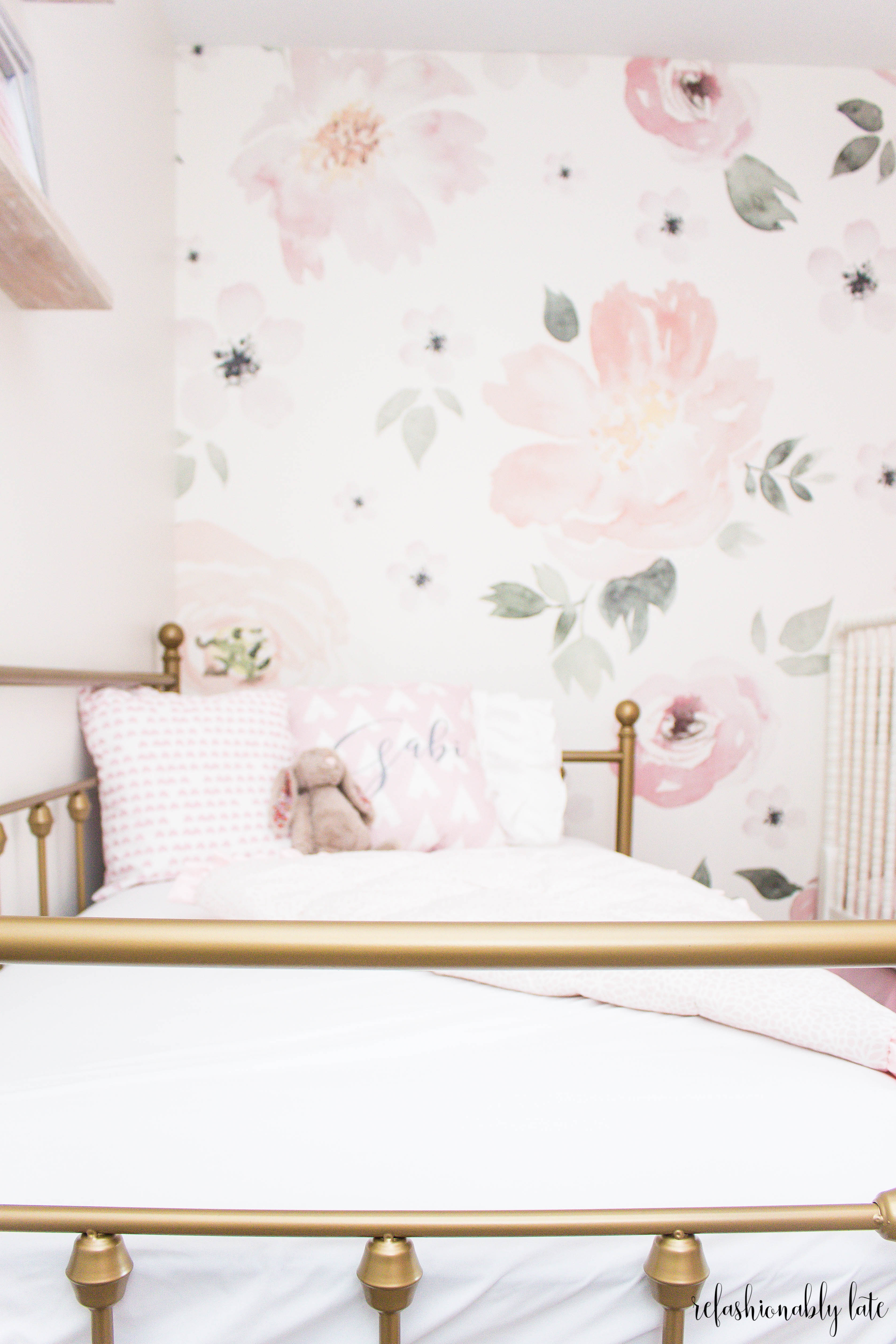 gold bed with white sheets and floral wall paper background