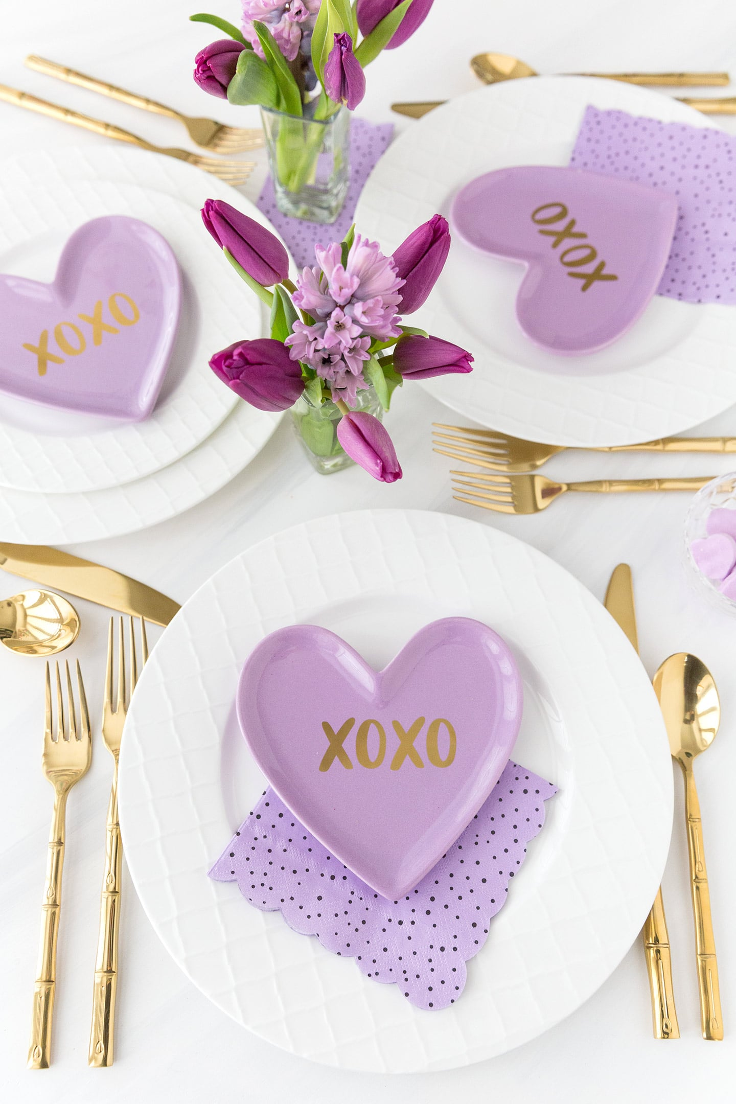 white table settings with purple heart plates on top with XOXO on them and gold silverware and purple flower centerpiece