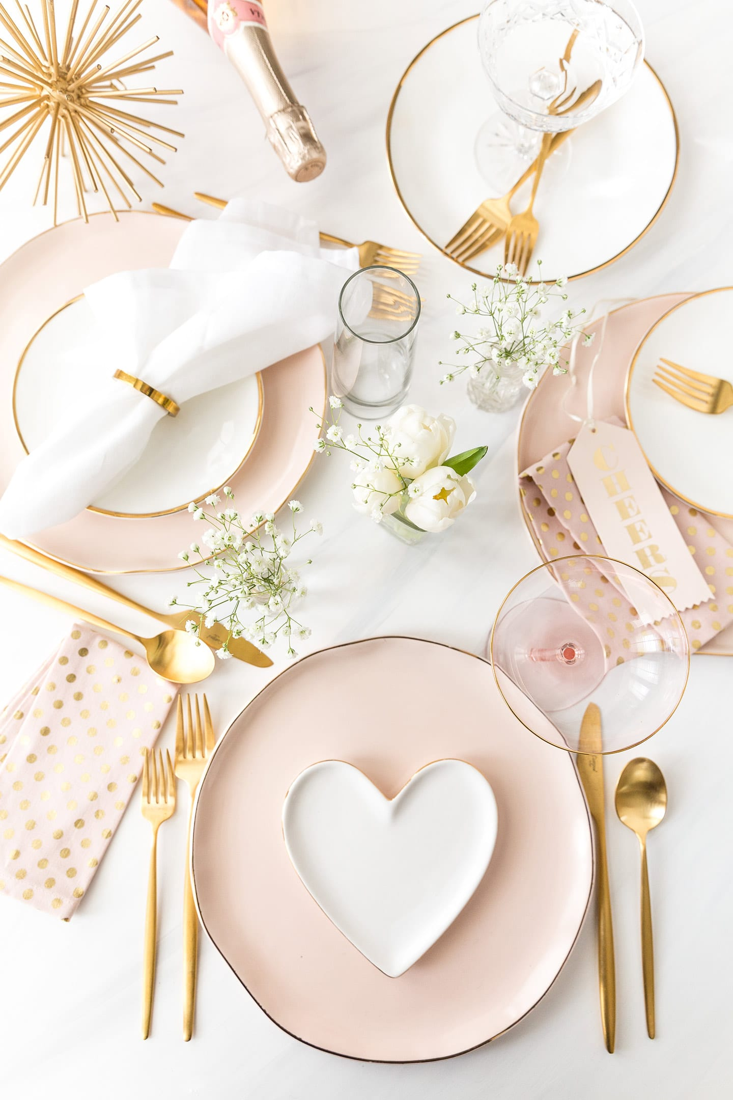 beautiful valentines day tablescape with light pink and white heart plates and gold silverware