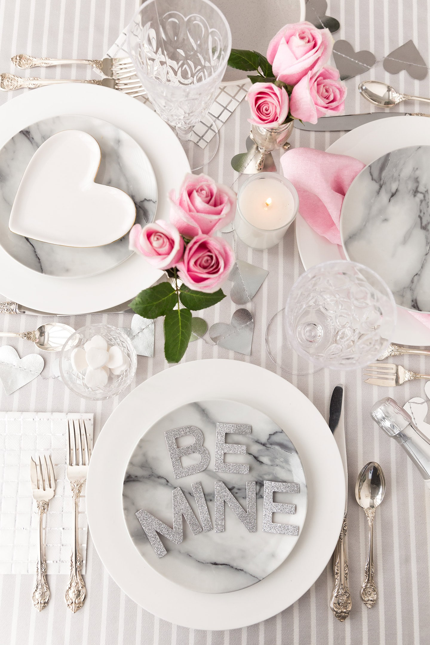 white striped tablecloth with white chargers and marble plates and a BE MINE sign on top of plate and pink roses in the center