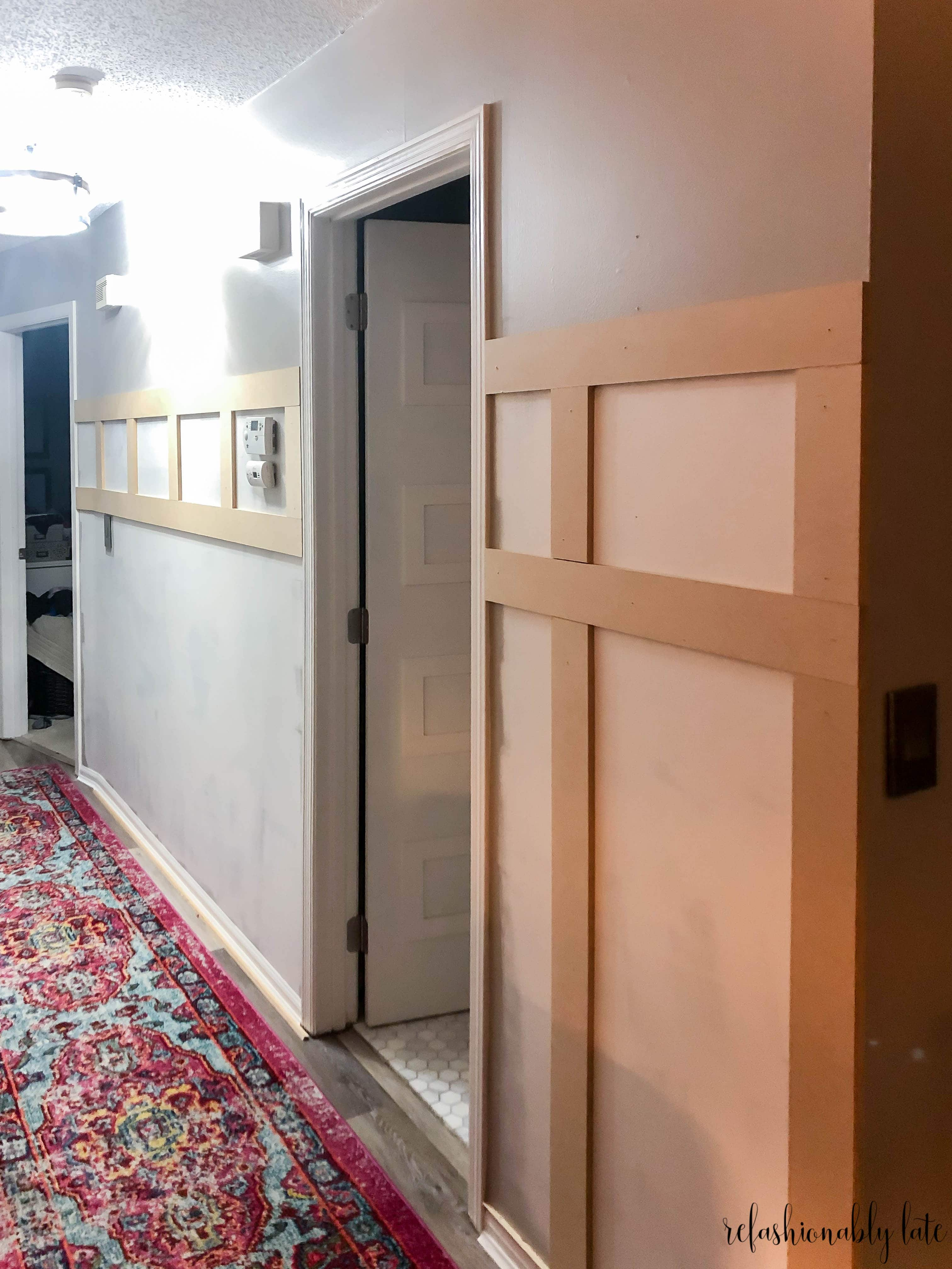 two horizontal MDF boards with vertical boards in between on a gray wall in a hallway