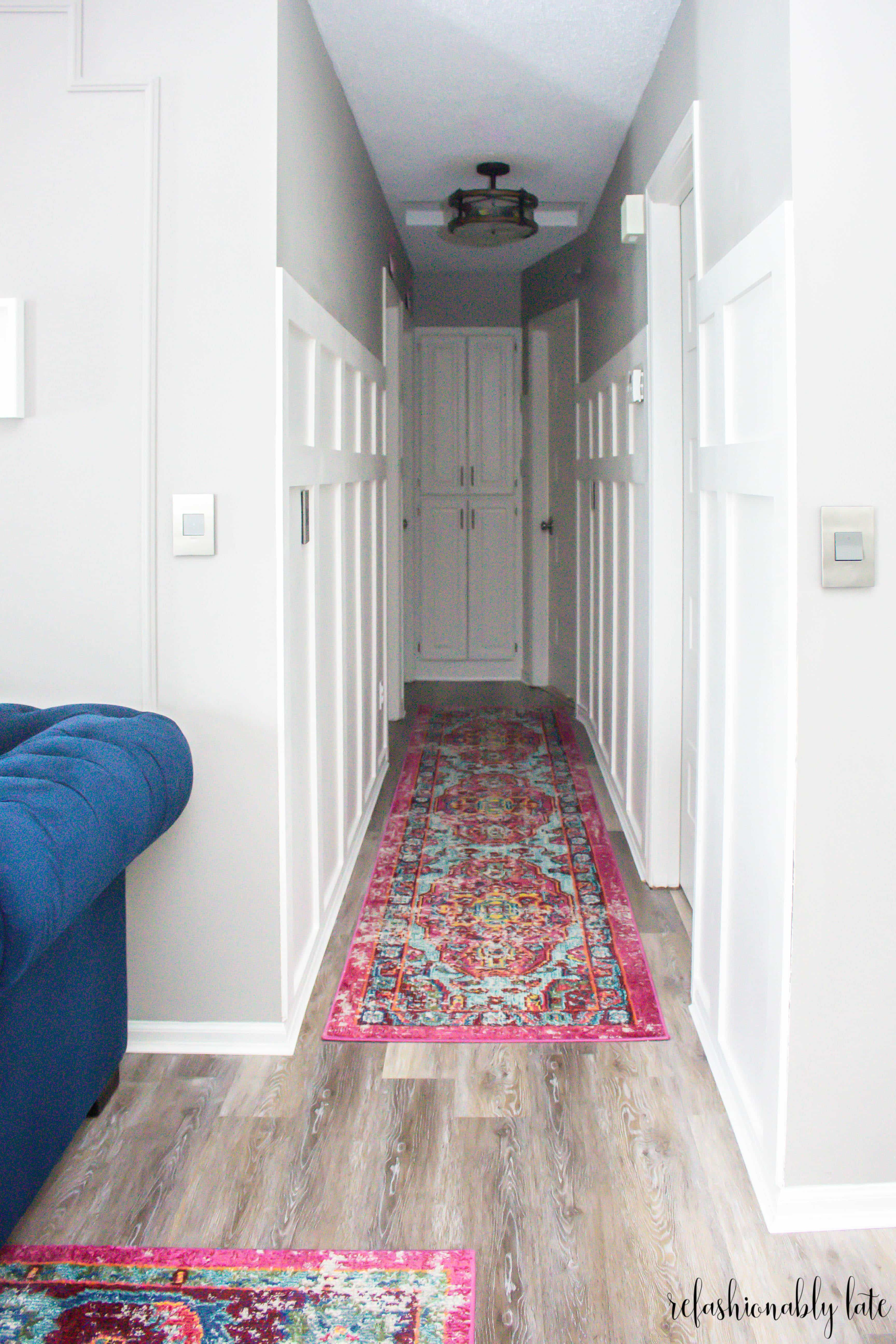 hallway board and batten with blue couch on the side with a colorful hallway runner rug